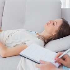Pensive woman lying on the couch while psychologist writing